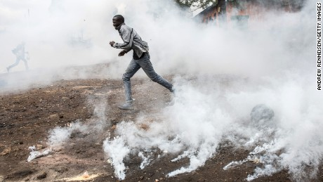 NAIROBI, KENYA - OCTOBER 26: A National Super Alliance (NASA) protestor runs from a tear gas canister in the Kibera slum on October 26, 2017 in Nairobi, Kenya. Protestors have Kibera boycotted the vote and are attempting to block polls during Kenya's controversial rerun election.  (Photo by Andrew Renneisen/Getty Images)