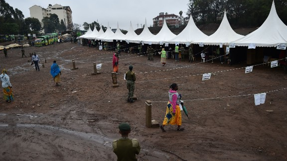 A police official looks on as residents walk into a polling station the Kibera slum area of Nairobi.
