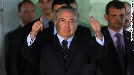 Brazilian President Michel Temer gestures while leaving the hospital in Brasilia on October 25, 2017. Temer had been hospitalized earlier today with urological problems, in the midst of a rowdy congressional debate over whether he should be removed from office and face a corruption trial.  / AFP PHOTO / EVARISTO SA        (Photo credit should read EVARISTO SA/AFP/Getty Images)