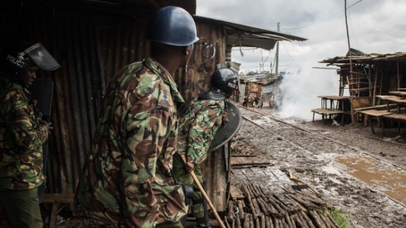 Police peer around a building after throwing tear gas at stone-throwing protesters in Kibera.