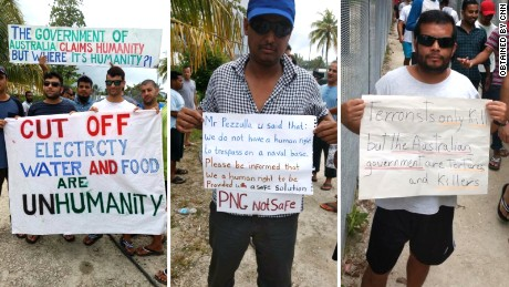 Manus Island refugees hold signs during a daily protest calling for the Australian government to find another solution.