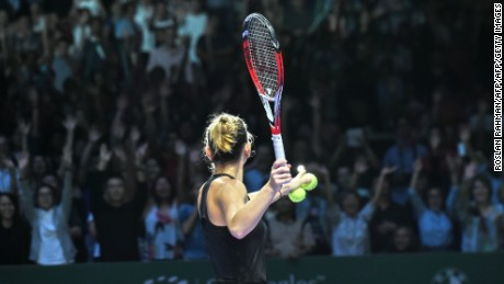 Simona Halep of Romania hits a ball for supporters after defeating Agnieszka Radwanska of Poland during the semi finals of the Women's Tennis Association (WTA) finals in Singapore on October 25, 2014. AFP PHOTO / ROSLAN RAHMAN        (Photo credit should read ROSLAN RAHMAN/AFP/Getty Images)
