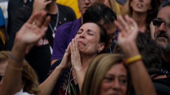 A protester appears to pray as she takes part in a rally outside the Catalan Parliament.