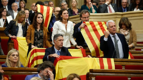 Opposition Catalan lawmakers place Spanish national flags and Catalan esteladas over the benches ahead of a vote on independence inside the Catalan Parliament in Barcelona, Spain.