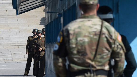 North Korean soldiers (L) look at the South side while US Secretary of Defence Jim Mattis and South Korean Defence Minister Song Young-Moo visit at the truce village of Panmunjom in the Demilitarized Zone (DMZ) on the border between North and South Korea on October 27, 2017.