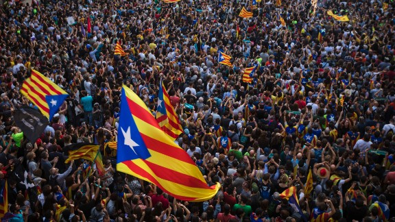 "People wave ""estelada,"" or pro-independence flags, outside the Palau de la Generalitat in Barcelona, Spain, on Friday, October 27, after Catalonia"