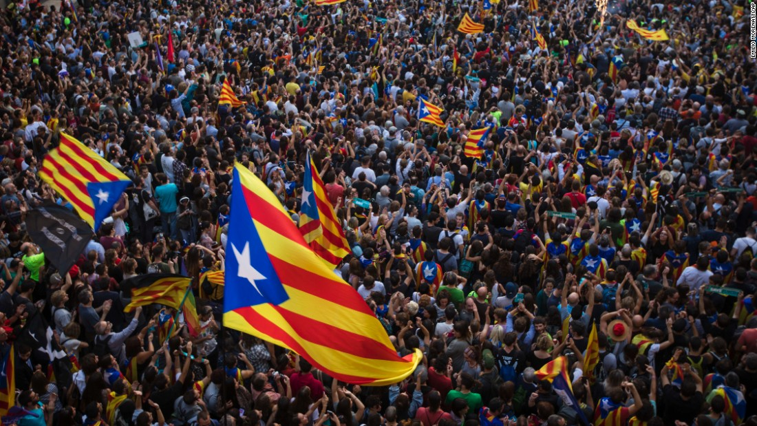 "People wave ""estelada,"" or pro-independence flags, outside the Palau de la Generalitat in Barcelona, Spain, on Friday, October 27, after Catalonia's regional Parliament <a href=""http://www.cnn.com/2017/10/27/europe/catalonia-independence-spain/index.html"">passed a motion</a> it says establishes an independent Catalan Republic."