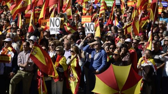 """People hold signs reading """"No to the coup"""" while waving Spanish flags during a demonstration urging unity in Madrid on Saturday."""