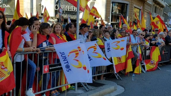 """Anti-independence protesters in Barcelona on Sunday holding Spanish flags, as well as others that say """"together."""""""