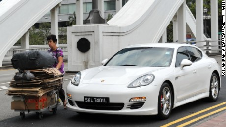 A woman pushes a trolly of recycle waste past a luxury car on the street in Singapore on march 4, 2014.