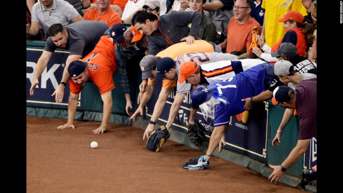 Fans reach for a foul ball in Houston during Game 5 of the World Series on Sunday, October 29.
