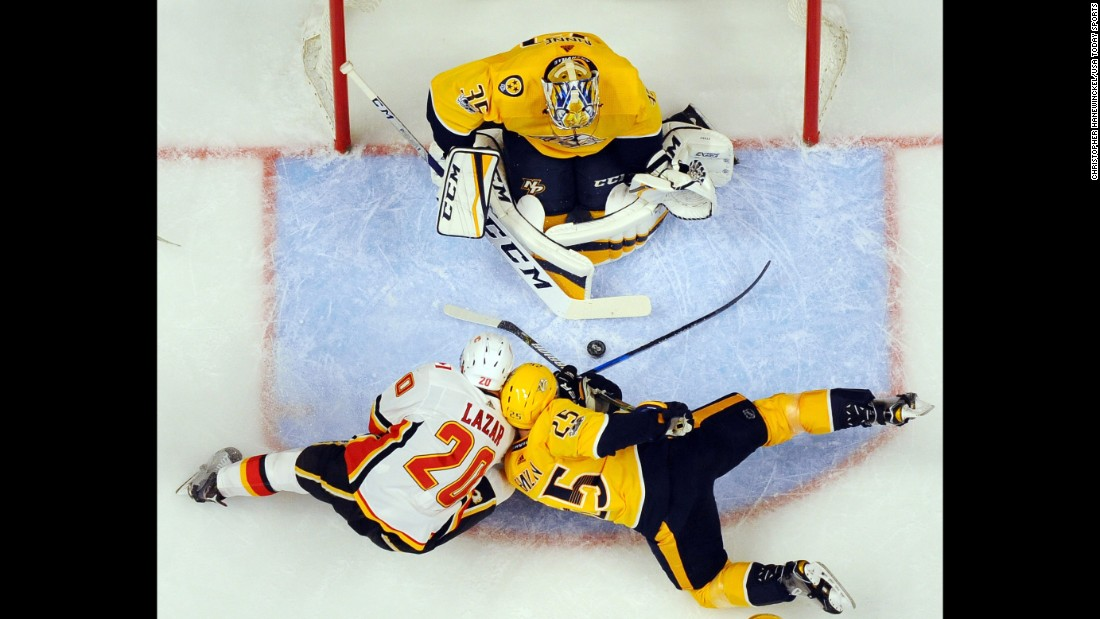 Nashville goalie Pekka Rinne makes a save as Calgary's Curtis Lazar and Nashville's Alexei Emelin collide in his crease on Tuesday, October 24.
