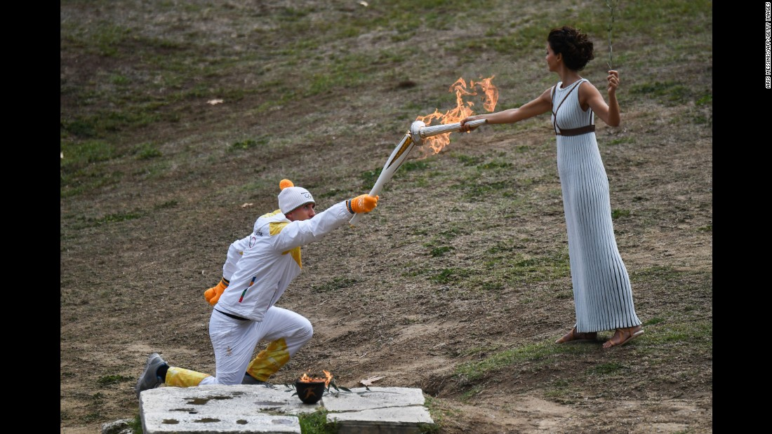 The Olympic torch begins its trip from Greece to PyeongChang, South Korea, as cross-country skier Apostolos Angelis takes the flame from actress Katerina Lechou on Tuesday, October 24.