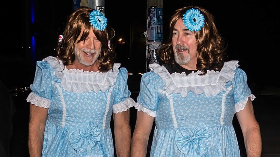 Bruce Willis, left, shows up as one of the Grady twins at director M. Night Shyamalan's Halloween party.