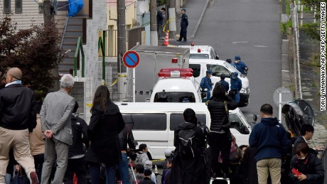 Media gather in front of an apartment (partialy covered with a blue sheet) where Japanese police found body parts in a suburb of Tokyo.
