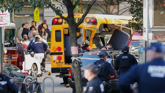 Four people on the school bus had minor injuries after the truck crashed into it, a police official said. After hitting the bus, the driver exited the truck and was shot by police while displaying imitation firearms, according to the NYPD.