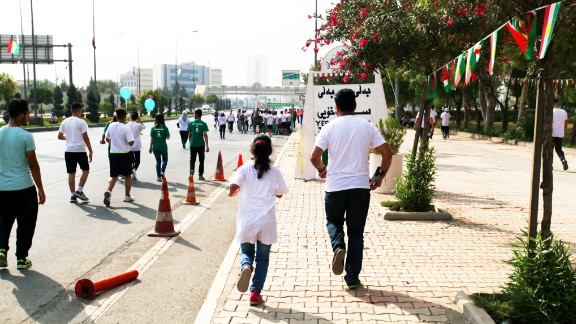 A father and daughter team run past signs advocating Kurdish independence.