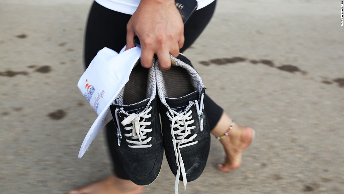A runner takes off shoes and walks barefoot after the long run.