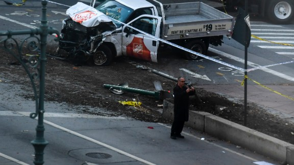 """An investigator takes pictures with his phone near a pickup truck following an incident in New York on October 31, 2017.  A pickup driver killed eight people in New York on Tuesday, mowing down cyclists and pedestrians, before striking a school bus in what officials branded a """"cowardly act of terror."""" Eleven others were seriously injured in the broad daylight assault and first deadly terror-related attack in America's financial and entertainment capital since the September 11, 2001 Al-Qaeda hijackings brought down the Twin Towers.  / AFP PHOTO / Don EMMERT        (Photo credit should read DON EMMERT/AFP/Getty Images)"""