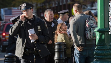 A young girl reacts as police officers block an area following a shooting incident in New York on October 31, 2017. Several people were killed and numerous others injured in New York when a suspect plowed a vehicle into a bike and pedestrian path in Lower Manhattan, and struck another vehicle on Halloween, police said. A suspect exited the vehicle holding up fake guns, before being shot by police and taken into custody, officers said.  / AFP PHOTO / Don EMMERT        (Photo credit should read DON EMMERT/AFP/Getty Images)