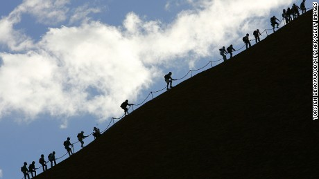 Tourists climb the monolith of Uluru to reach the 340m summit.