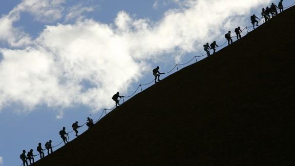 Tourists climb the monolith of Uluru to reach the 340m summit.