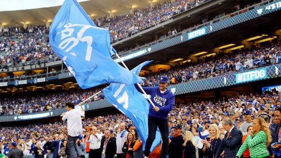 Actors Rob Lowe, right, and Ken Jeong wave Dodger flags on top of a dugout before the game. Many celebrities were in attendance.