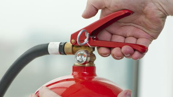white hand presses the trigger fire extinguisher; Shutterstock ID 115760446; PO: CNN Photos