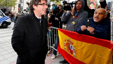 Dismissed Catalonia's leader Carles Puigdemont walks past Spanish flag as he arrives to address a press conference at The Press Club in Brussels on October 31, 2017.  Catalonia's dismissed leader Carles Puigdemont along with other members of his dismissed government addressed a press conference at The Press Club in Brussels on October 31, 2017, a day after he arrived in Belgium as Spanish prosecutors demanded he be charged with rebellion after the region's parliament declared independence. / AFP PHOTO / BELGA / NICOLAS MAETERLINCK / Belgium OUT        (Photo credit should read NICOLAS MAETERLINCK/AFP/Getty Images)