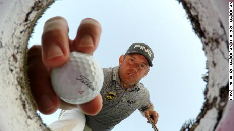 DUBAI, UNITED ARAB EMIRATES - JANUARY 27:  Lee Westwood of England takes a ball out of a golf hole on the putting green during a practice round prior to the Omega Dubai Desert Classic at the Emirates Golf Club on January 27, 2015 in Dubai, United Arab Emirates.  (Photo by Ross Kinnaird/Getty Images)