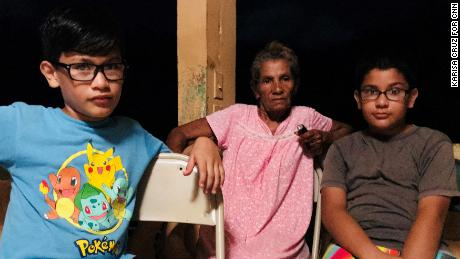 Members of the Rivera family sit in their powerless home in Manati, Puerto Rico.