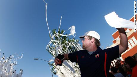 An Auburn fan throws a roll of toilet paper at Toomer's Corner.