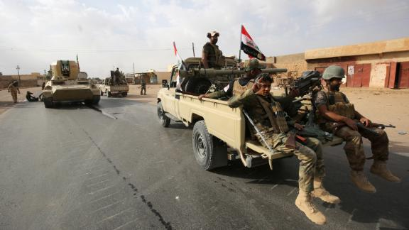 Iraqi forces and members of the Hashed al-Shaabi (popular mobilization units) enter Qaim on Friday.