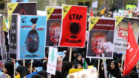 Iranian women carry placards during a protest Saturday outside the former US Embassy in Tehran.