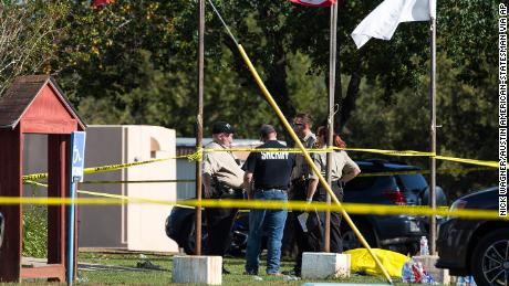 Law enforcement officials stand next to a covered body at the scene of a fatal shooting at the First Baptist Church in Sutherland Springs, Texas, on Sunday, Nov. 5, 2017. (Nick Wagner/Austin American-Statesman via AP)