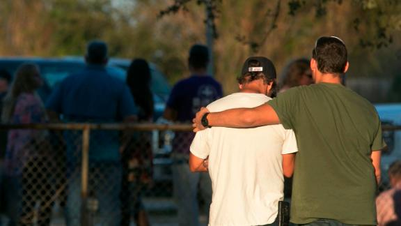 People comfort each other at a community center near the scene of the deadly shooting.