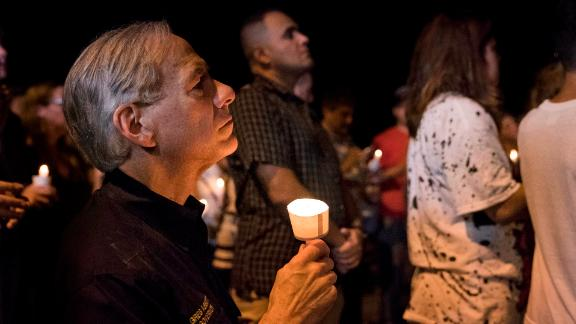 Texas Gov. Greg Abbott participates in a candlelight vigil Sunday for the victims at First Baptist Church.