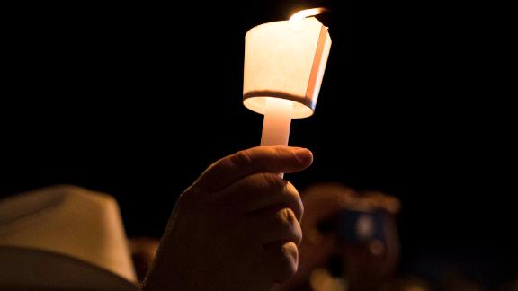 A mourner holds a candle during a vigil held for the victims of a fatal shooting at the First Baptist Church of Sutherland Springs, Sunday, Nov. 5, 2017, in Sutherland Springs, Texas. (AP Photo/Darren Abate)