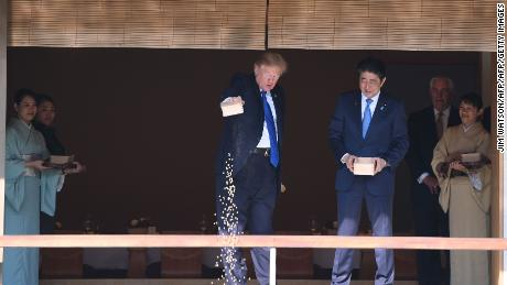 "US President Donald Trump (C) feeds koi fish as Japanese Prime Minister Shinzo Abe (R)looks on during a welcoming ceremony in Tokyo on November 6, 2017. Trump lashed out at the US trade relationship with Japan, saying it was ""not fair and open"", as he prepared for formal talks with his Japanese counterpart. / AFP PHOTO / JIM WATSON        (Photo credit should read JIM WATSON/AFP/Getty Images)"