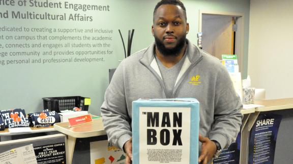 "Rahk Lash holds a physical replica of the ""man box."""