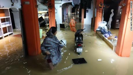 Residents stand inside their flooded home in Hoi An on Monday.