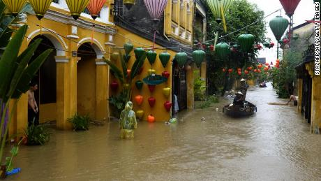 Local residents navigate on a boat as others wade in the flooded town of Hoi An on Sunday.
