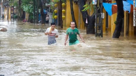 Local residents wade through flood waters at the central tourist town of Hoi An on November 6, 2017.