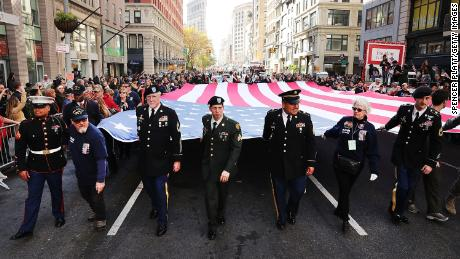 Caption: NEW YORK, NY - NOVEMBER 11: Veterans and others carry a large American Flag while marching in the nation's largest Veterans Day Parade in New York City on November 11, 2016 in New York City. Known as 'America's Parade' it features over 20,000 participants, including veterans of numerous eras, military units, businesses and high school bands and civic and youth groups.