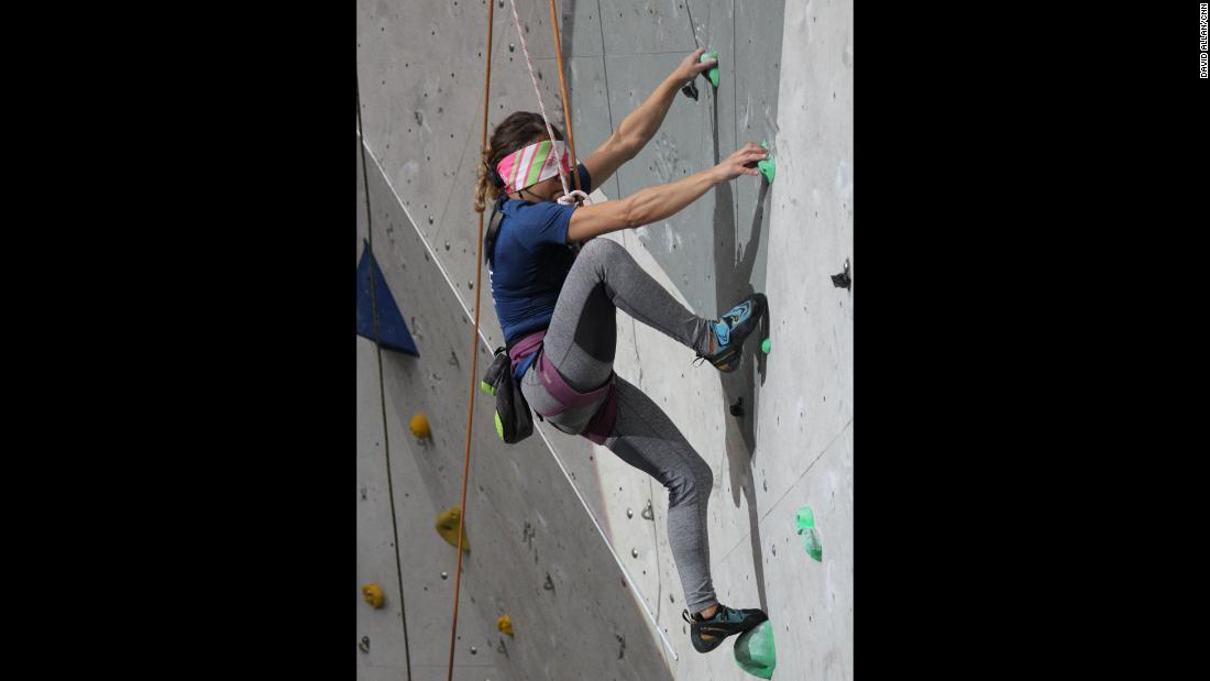 Communicating by headset, guides describe to blind climbers where their feet and hands are in relation to a given hold.