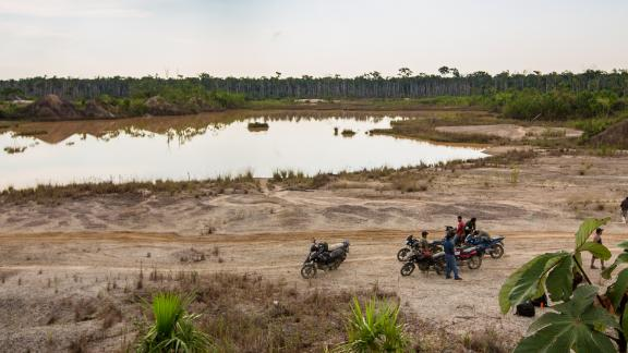 """A group of motorcycle taxis known as """"Los Tigres"""" stops near a toxic mining site in the Peruvian Amazon."""