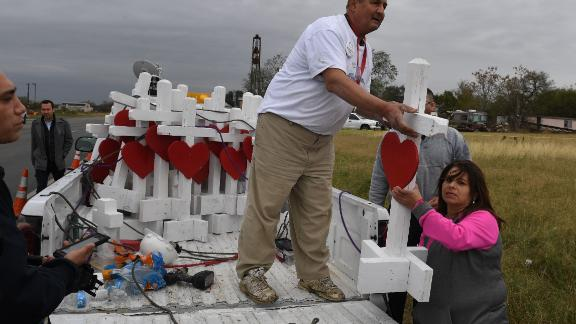 Carpenter Greg Zanis (C) who drove from Chicago unloads his crosses outside the First Baptist Church which was the scene of the mass shooting that killed 26 people in Sutherland Springs, Texas on November 8, 2017. A gunman wearing all black armed with an assault rifle opened fire on a small-town Texas church during Sunday morning services, on November 5, killing 26 people and wounding 20 more in the last mass shooting to shock the United States. / AFP PHOTO / MARK RALSTON        (Photo credit should read MARK RALSTON/AFP/Getty Images)
