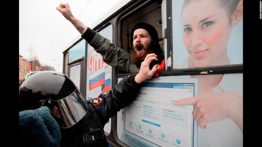A detained member of the Other Russia movement shouts from a police bus in St. Petersburg, Russia, during an unauthorized rally to mark the centenary of the Bolshevik Revolution on Monday, November 6.