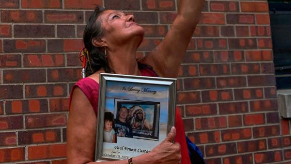 Lynn Eagle Feather holds a bouquet to the sky while clutching a picture in memory of her son Paul Castaway.