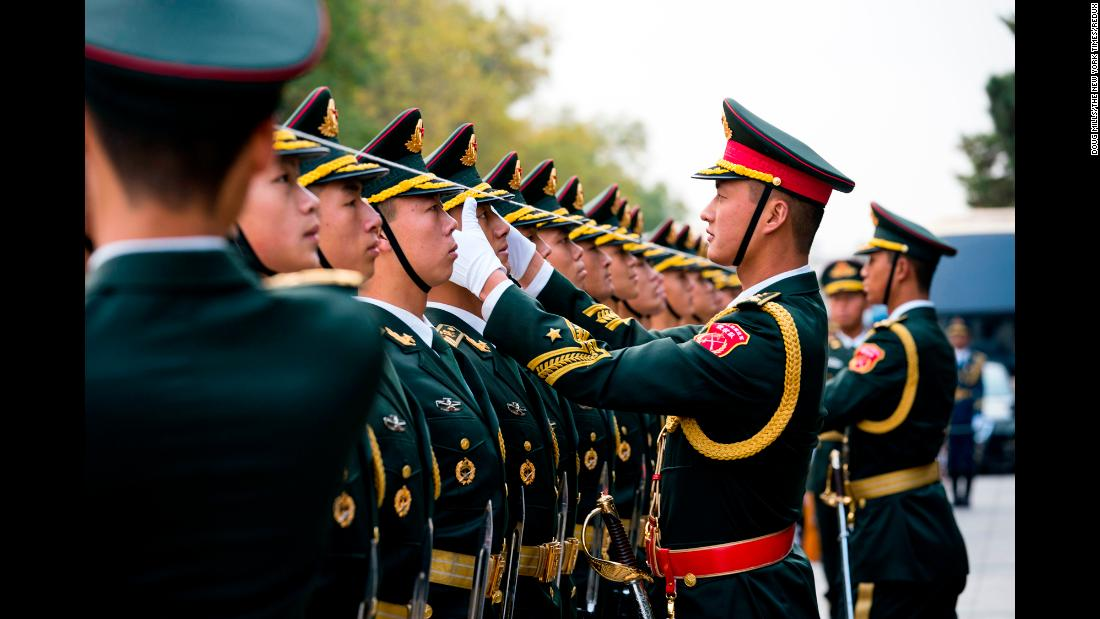 Chinese officers use a string to align the caps of members of an honor guard before the start of a welcome ceremony for US President Donald Trump and first lady Melania Trump in Beijing, on Thursday, November 9.
